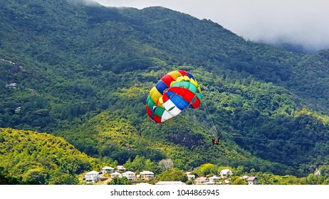 Colorful Parasailing screen in front of the green mountains on the coast of Seychelles
