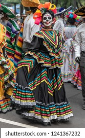 Colorful participants in the festival of the Day of the dead in Mexico. Attractive skull costumes worn by dancing Mexican girls
