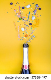 Colorful party attributes fly out from botle of champagne wine. on a yellow background. Flat lie. Celebrate concept. High resolution photo.