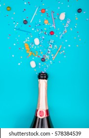 Colorful party attributes fly out from botle of champagne wine. on a blue background. Flat lie. Celebrate concept. High resolution photo.