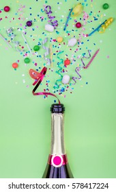 Colorful party attributes fly out from botle of champagne wine. on a GREEN background. Flat lie. Celebrate concept. High resolution photo.