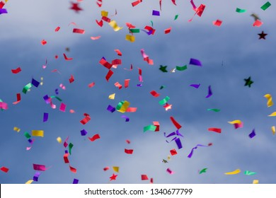 Colorful party confetti against a bright blue sky.