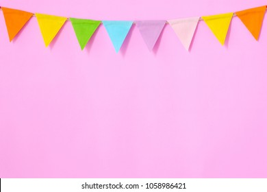 Colorful party flags hanging on pink background, birthday, anniversary, celebrate event, festival greeting card background