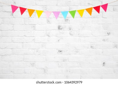 Colorful party flags hanging on white brick wall  background, birthday, anniversary, celebrate event, festival greeting card background
