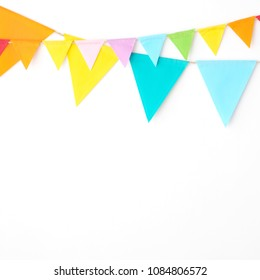 Colorful party flags hanging on white wall  background, birthday, anniversary, celebrate event, festival greeting card background