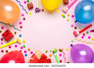 Colorful party frame with red gift box with various party confetti, balloons, streamers, pokers and decorations on pink background. Holiday card Flat lay Top view Happy Birthday party concept
