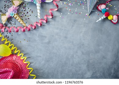 Colorful party supplies and accessories bordering top left corner of blackboard for festive occasion