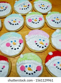 Colorful Pastel Decorated Snowman and Snowwoman circle cookie cutter round face cookies with sugar sprinkle stocking caps or hats celebrate winter in January or Christmas