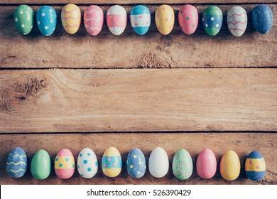 Colorful pastel easter eggs on wooden board background with space. Vintage toned.
