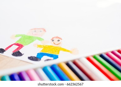 Colorful pastel oil crayons and children's drawing of father with son