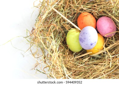 Colorful pastel tone chocolate easter eggs in a nest made of straw in top of a white sheet