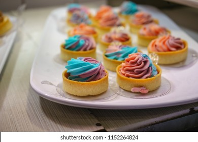 Colorful pastry treats whipped up with vibrant icing and lined up in rows on a perfect white platter.