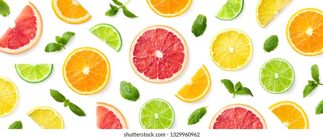 Colorful pattern of citrus fruit slices and mint leaves isolated on white background. Top view, flat lay