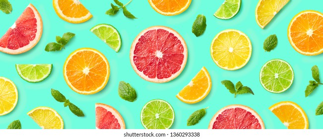 Colorful pattern of citrus fruit slices and mint leaves on blue background. Top view, flat lay