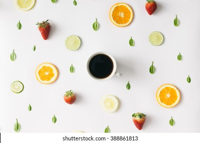Colorful pattern made of citrus fruits, leaves and strawberries with cup of coffee