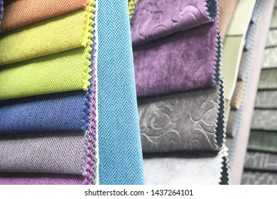 Colorful patterns of upholstery fabric. Close-up of samples of furniture fabric. Multicolored soft velour. Furniture industry. Background texture.