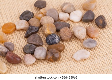 Colorful pebbles on beige fabric background.