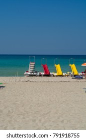 Colorful pedal-boats with water slides on the beach.