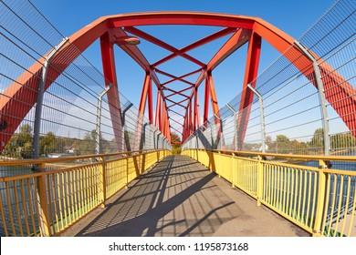 Colorful pedestrian bridge over a canal in bright sunlight.