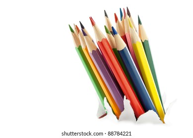 Colorful pencils breakthrough the white paper, isolated on white.