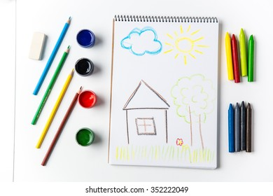 Colorful pencils and brushes lying around scketchbook with kids crayon drawing of home, cloud, tree and sun