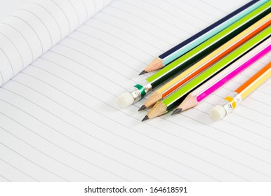 Colorful pencils on notebook