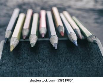 Colorful pencils over mini blackboard