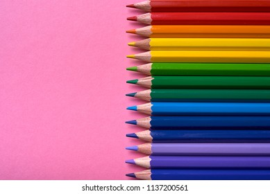 Colorful pencils of rainbow colors on pink pastel background, close up. Set of colorful pencils, copy space. Crayons. Top view, flat lay. Back to school, college concept. Abstract background