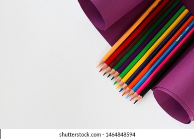 colorful pencils for school are on a purple cardboard