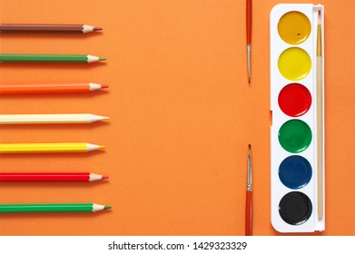 Colorful pencils and watercolors as frame on textured orange paper as background. Top view, flat lay.