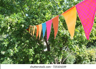 A colorful pennant chain hanging in the trees for a celebration / party.
