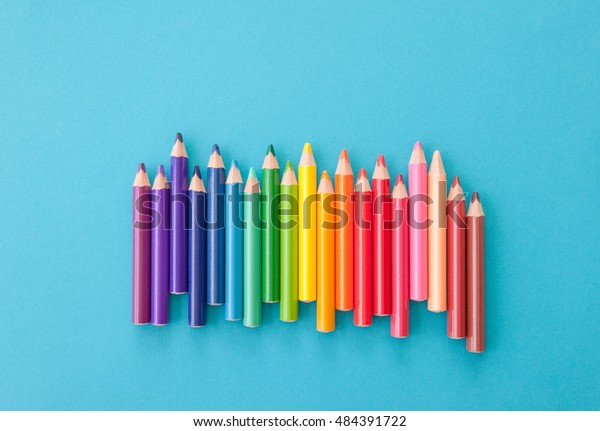 Colorful pens in colors of the rainbow on blue