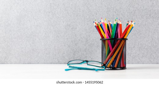 colorful pens in a quiver with glasses on a desk with gray background