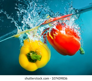 colorful peppers splashing into blue water