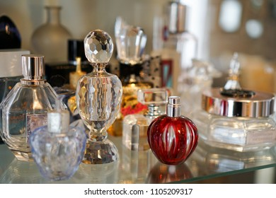 Colorful perfume glass bottles on shelf with various shapes and sizes