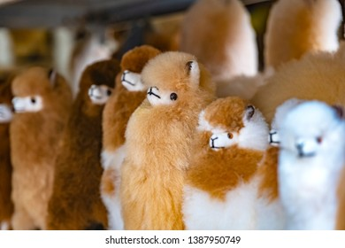 Colorful Peruvian fluffy white and brown toy lama souvenir for sale at street Indian market in Miraflores, Lima.