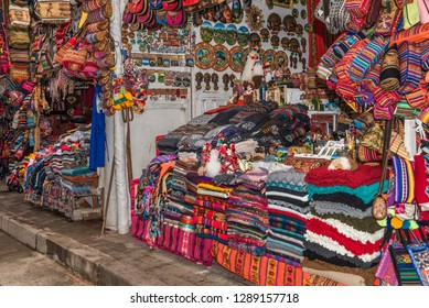 Colorful peruvian market with textiles and handbags for sale