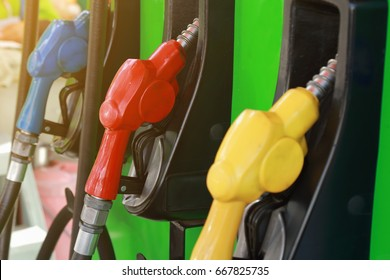 Colorful Petrol pump filling nozzles  , Gas station in a service in warm sunset.