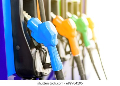 Colorful Petrol pump filling nozzles isolated on white background , Gas station in a service in warm sunlight