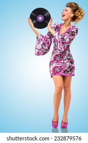 Colorful photo of a happy fashionable hippie homemaker with a retro vinyl record in her hands on blue background.