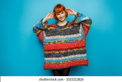 Colorful photo of young smiling female model wear oversize sweater isolated on blue background