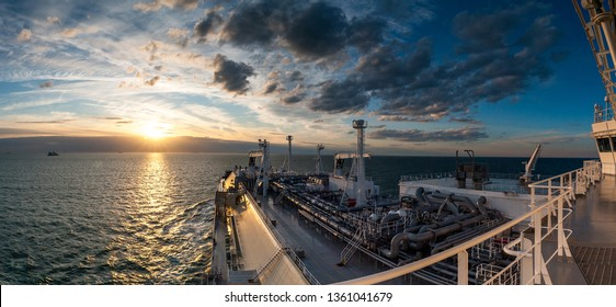 Colorful photograph of huge LNG carrier sailing towards beautiful sunset. The sky is full of colored clouds and the sun is just above the horizon.