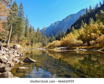 Colorful photograph of Yosemite National Park in fall with a river, forest and mountains in the background.