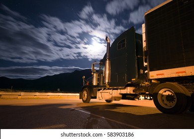 Colorful picture of a black semi truck and a reefer trailer standing in the parking lot at night, lit a lantern and moonlight through the transparent clouds.