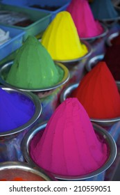 Colorful piles of Indian bindi powder dye at outdoor local market in India blue, yellow, red, green, pink, and purple