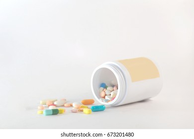 colorful pill and capsule of drug with white drug bottle and yellow label on the white background