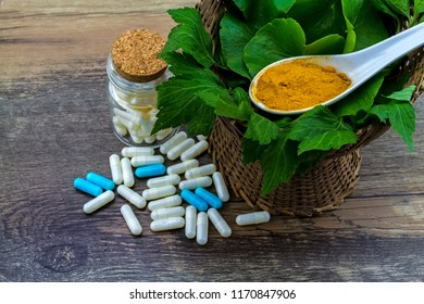 Colorful pill and yellow turmeric powder and green leaf of   White mugwort plant (Artemisia lactiflora) with Green Asiatic Pennywort (Centella asiatica ) on grunge wooden background.