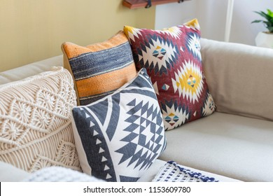 colorful pillow with native american pattern on biege sofa in living room.