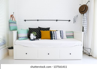 Colorful pillows on a sofa with white brick wall in background