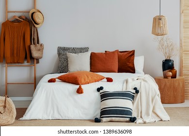 Colorful pillows on white bed of classy bedroom with round wooden bedside table and ladder